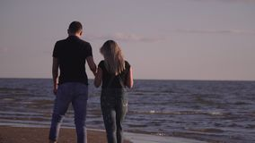 He guy embrace and kiss the girl on the beach. Lovely couple have a rest on the beach. The loving couple walks on the stock footage