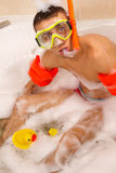 Guy is enjoying a bath in mask with snorkel. Royalty Free Stock Photography