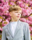 Guy enjoying cherry blossom sakura. Sakura garden concept. Confident stylish child enjoy warm spring day. Boy. Fashionable teen posing near sakura. Child pink royalty free stock image