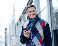 Guy enjoying music on street. Young man listening to music on mobile phone Royalty Free Stock Photo
