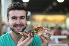 Guy enjoying some pizza and smiling Royalty Free Stock Images