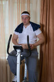 Guy exercising on stationary training bicycle and looking at his fat stomach. Guy exercising on stationary training bicycle at home and looking at his fat Stock Photography