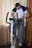 Guy exercising on stationary training bicycle and looking at his fat stomach. Guy exercising on stationary training bicycle at home and looking at his fat Stock Photo