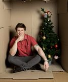 Guy is expressing gladness inside little carton box. Happy new year concept. Full length portrait of happy young man is sitting on floor ine confined cardboard royalty free stock images