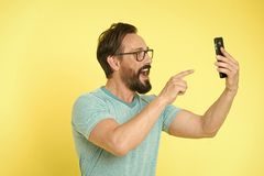 Guy eyeglasses cheerful pointing at smartphone. Man happy user interact application for smartphone. Guy bearded interact. Mobile interface application. Man royalty free stock photo