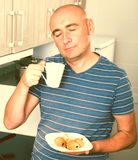 Guy with eyes closed drinking coffee and croissants in the morning. Sleepy guy with eyes closed drinking coffee and croissants in the morning royalty free stock image