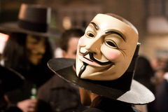 Guy Fawkes. A photo showing people wearing the Guy Fawkes mask on their face and on their hat. This mask has been popularized due to the movie V for Vendetta Royalty Free Stock Photography