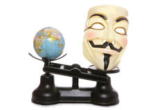 Guy fawkes mask on scales with a globe Stock Photo