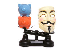 Guy fawkes mask with two piggy banks. On a white background Stock Photography