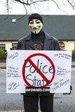 Guy Fawkes masked man. Spokane, Washington USA - December 20, 2014. A protestor in a Guy Fawkes mask displays a sign at a rally in Spokane Valley, Washington Royalty Free Stock Photography