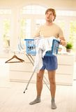 Guy fed up with housework. Tired young guy standing at home fed up with housework, looking up, holding washing basket Royalty Free Stock Image