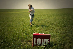 Guy in the field looks in suitcase with the word love Stock Images
