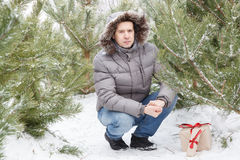 The guy among fir-trees with a gift Royalty Free Stock Photo