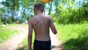 The guy after fishing is on a forest road. In the hands of holds net. Hot summer day. Summer vacation in the village. Summer vacation in the village. The guy stock video footage