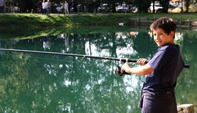 Guy with the fishing rod on the shores of Lake fishing Stock Photos