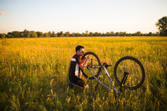 The guy fixing the bicycle wheel in the field at sunset Stock Image