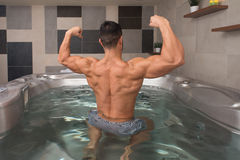 Guy Flexing Muscles in Azure Jacuzzi Stock Fotografie
