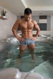 Guy Flexing Muscles in Azure Jacuzzi Stock Foto's