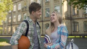 Guy flirting with pretty female student, proposing girl go to the cinema. Stock footage stock footage