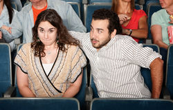 Guy Flirting in Theater. Guy in beard flirts with young women in theater Royalty Free Stock Photos