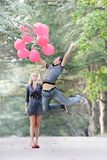 Guy is flying away, girl is holding him Royalty Free Stock Images