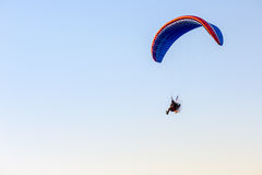 Guy flying on the clearly blue sky by paramotor. Blue kite,extreme activity port. feel freedom like birds. concept overcome the limits of human physiology Royalty Free Stock Images