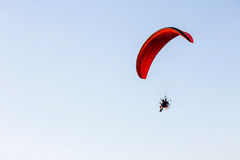 Guy flying on the clearly blue sky by paramotor. Red kite,extreme activity port. feel freedom like birds. concept overcome the limits of human physiology royalty free stock photo