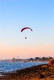 Guy flying on the clearly blue sky and wonderful beach by paramotor. Red kite,extreme activity port. feel freedom like birds. concept overcome the limits of Stock Photography