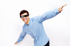 Guy flying in 3D glasses. Young hispanic man wearing jeans shirt and 3D TV LCD shutter glasses laughing and having fun with hands outstretched lifted upwards stock images