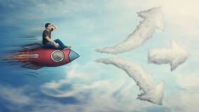 Guy flying on a fast rocket ship, hand to forehead looking far away for destination, has to choose a way as cloud arrows leads to. Three different directions royalty free stock photography