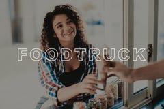 Guy In Food Truck Gives glass till unga flickan royaltyfria bilder