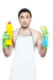 Guy forced to clean. Sad young man in apron holding cleaning sponge and bottle isolated on white Stock Images