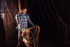 Guy freed from captivity and selecting from ropes Royalty Free Stock Photography