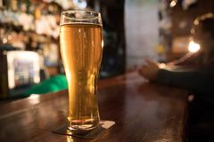 Guy friends drinking beer on the background. Full pint of beer in focus. Only hands shown stock images