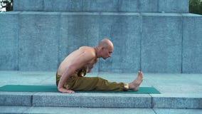 Guy Fulfills Yoga Gymnastics novo no parque da cidade na placa do granito video estoque