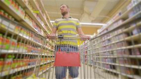 Guy with full supermarket trolley approaching camera and smiling happily, young man chooses products in the supermarket. Man buys drinks in store, man with a stock video