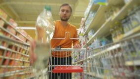 Guy with full supermarket trolley approaching camera. Young man chooses products in the supermarket, man buys drinks in store, HD stock video footage