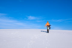 Guy in funny cap with a snowboard goes up the sand dune Royalty Free Stock Photo