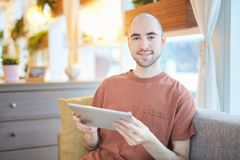 Guy with gadget. Young attractive man in t-shirt relaxing in cafe or at home with tablet Royalty Free Stock Photos