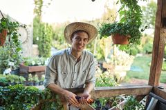 Guy gardener in a straw hat is standing next to a wooden veranda with a lot of plants on a sunny day. stock photography