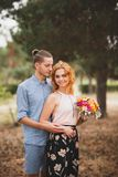 Happy young couple spending time outdoor in the autumn park. The guy gave flowers to a beautiful girl with red hair. royalty free stock photos