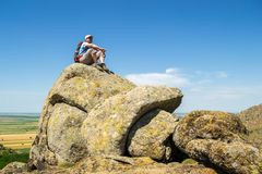 Guy gazing in the distance, while standing on top of a strange rock formation, during an Autumn hike. With very hot weather, in Macin mountains, Romania royalty free stock images