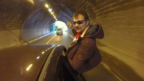 Guy gets out of window and sits on its frame, car exiting tunnel at high speed. Stock footage stock video