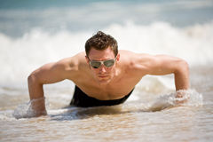 Guy getting up from the beach. Young Caucasian hunk up from the sandy beach with sunglasses Stock Photos