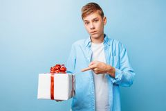 Guy with a gift in his hands for Valentine`s Day, on a light blue background stock images