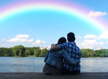 The guy with the girl admiring nature after rain. Two young man and woman looking at the rainbow on the background of the urban landscape and blue sky with royalty free stock photography