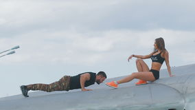 Guy and girl in army style clothing climbed on the old plane. stock video footage