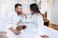 The guy and the girl bathrobe, girl feeds the guy fruit. The guy and the girl bathrobe. The girl feeds the guy fruit stock image