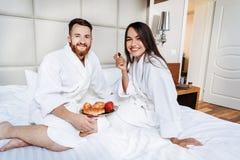 The guy and the girl bathrobe, girl feeds the guy fruit. The guy and the girl bathrobe. The girl feeds the guy fruit stock photos