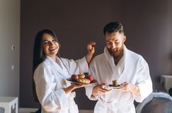 The guy and the girl bathrobe, girl feeds the guy fruit. The guy and the girl bathrobe. The girl feeds the guy fruit stock images